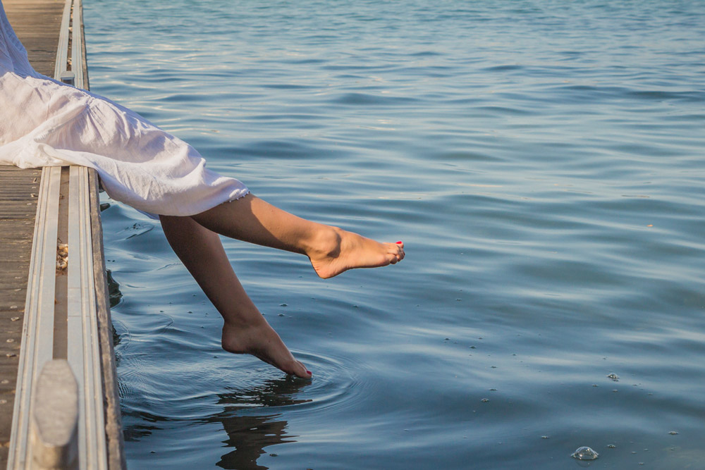 A young woman let her legs dangle from pier