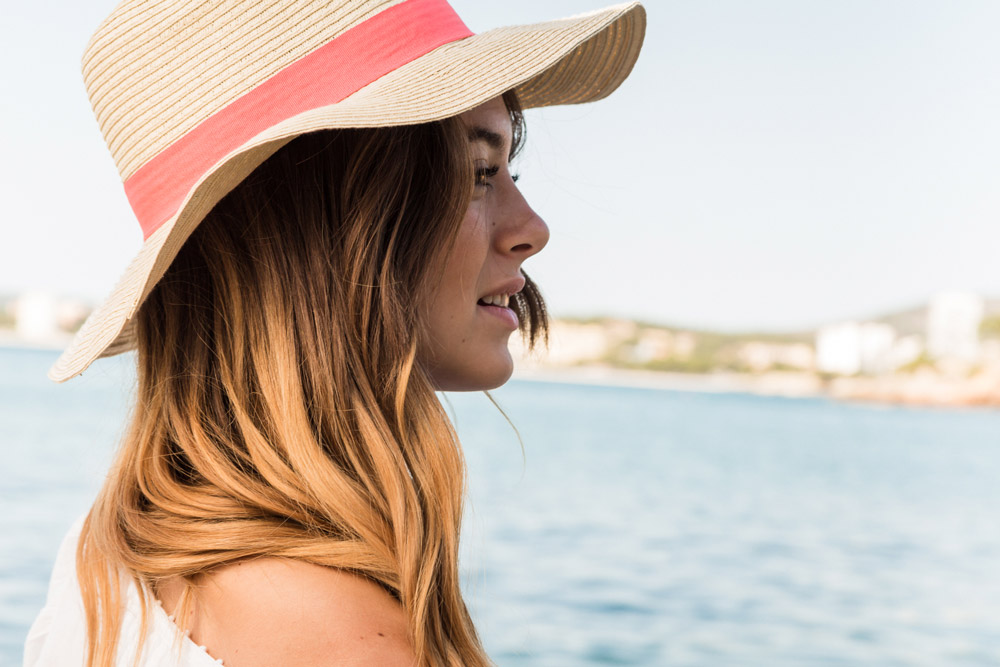 A young woman with beautiful hair is wearing a sun hat, looking to the sea