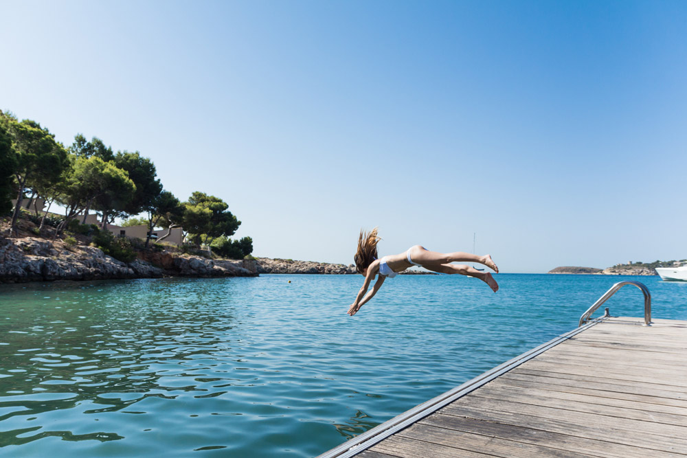 Young woman is jumping into the sea.