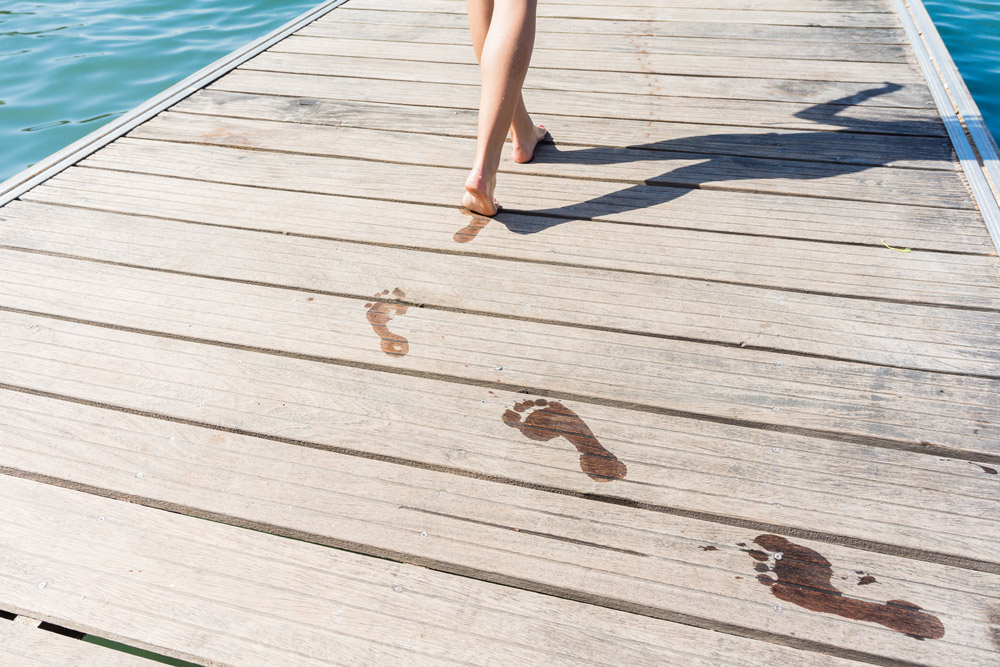 A young woman´s footprints on a pier next to the sea.