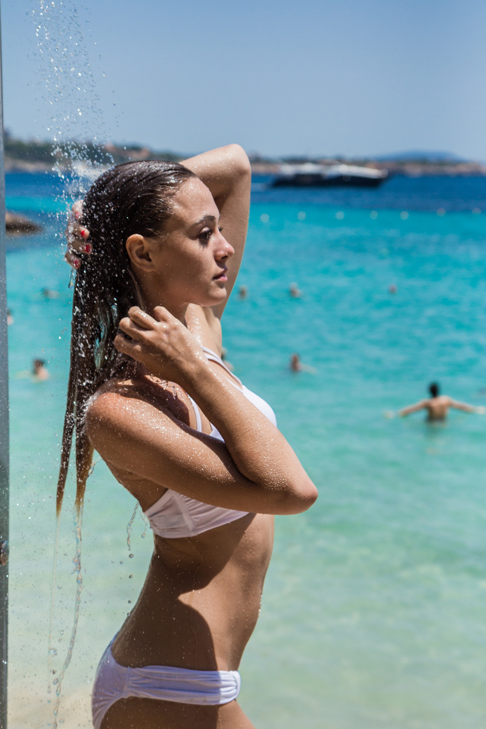 A young woman showering her hair next to the sea.